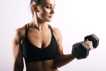 Portrait of muscular fitness woman with perfect athletic body in sports black bra holding dumbbells in strong hand. Shooting in professional studio on white isolated background Stock Photo - 129612135