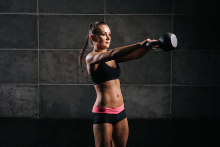 Portrait of muscular young woman with perfect athletic body in black sportswear swinging kettlebell, on black isolated background. Sporty muscular girl is looking away