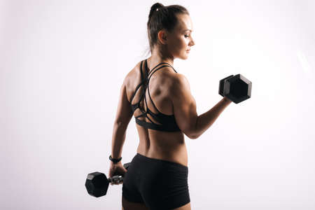 Back view portrait of young woman with perfect athletic body in sports black bra. Working out with a heavy dumbbell on isolated white background Stock Photo