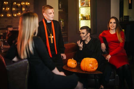 Bunch of friends have fun and carefree time celebrating Halloween. Group of young people sitting in cafe in festive costumes and celebrating an autumn holiday. Carved pumpkin on the table.