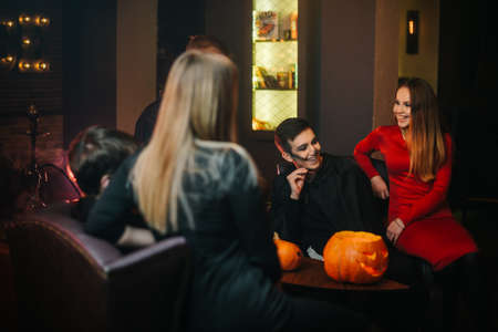 Bunch of friends from two guys and two girls having fun celebrating Halloween in a dark cozy cafe. Carved pumpkin on the table. Colorful make-up of young people.