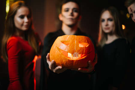Group of friends celebrating Halloween. Guy wearing zombie costume holds pumpkin on his outstretched arm. Two beautiful girls looking at pumpkin. Peoples faces are blurred, camera focuses on pumpkin
