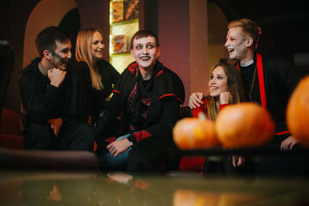 Young man in a festive priest costume hugs his girlfriend at a Halloween meeting of friends in a cafe. The guy in the image of Count Dracula tells terrible stories.