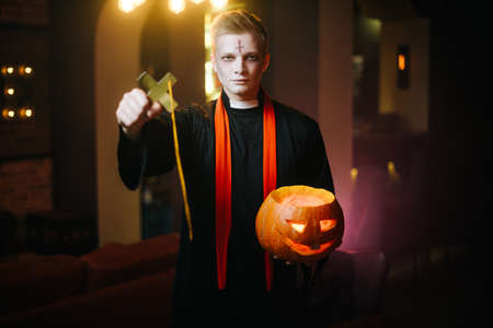 Young man in a Halloween priest costume holds a festive carved pumpkin and a large religious black cross. The guy in the form of a priest looks at the camera Stock Photo