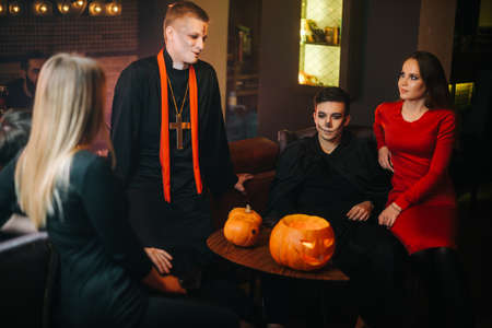 Portrait of group young people in colorful Halloween costumes sitting and chat in a cozy cafe. Carved pumpkin on the table. Imagens