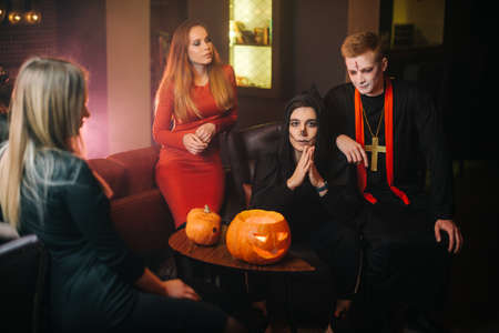 Group of friends in beautiful costumes and colorful makeup celebrate Halloween together in a cozy dark cafe. Holiday carved pumpkin on the table