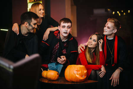 Group of five friends are celebrating Halloween in a cafe. Guys dressed as scary holiday monsters and dressed in colorful costumes. Carved pumpkin with candle inside on table Imagens