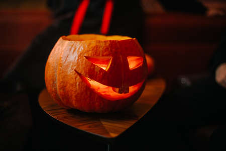 Halloween carved pumpkin with a burning candle inside on the table. Symbol of a holiday surrounded by a friendly company celebrating in a cafe Imagens