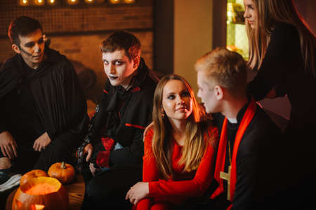 Guy in Count Draculas Halloween costume is sitting with friends in a cafe and looking at the camera