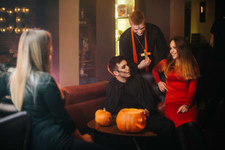 Group of friends are celebrating Halloween in cafe. Guy is dressed as terrible priest and monster. Beautiful sexy girl in a red dress sitting on sofa. Shooting in room with black and red walls