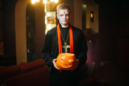 Young man in Halloween priest costume holding carved pumpkin in front of camera.