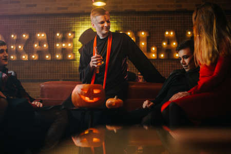 Friends in costumes conversation at the halloween party. Beautiful girl in company of two guys in a cafe. Holiday carved pumpkin on table
