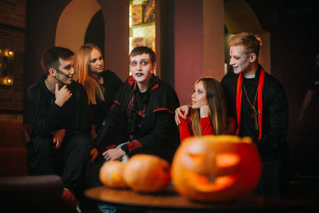 Young people are celebrating Halloween in cafe. Group of young cheerful guys and girls dressed in holiday costumes are sitting in room with red walls. Carved pumpkin on table Imagens