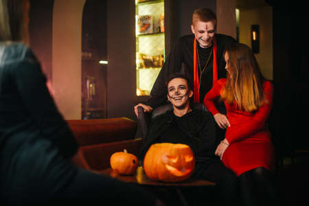 Group of four friends are celebrating Halloween in a cafe. Guys dressed as scary holiday monsters. Carved pumpkin on table. Imagens
