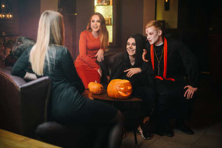 Bunch of four friends having fun celebrating Halloween at cafe. Guy is dressed as terrible priest and monster. Beautiful sexy girl in red dress. Carved pumpkin on table Imagens