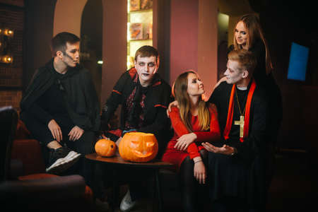 Guy in Count Draculas Halloween costume is sitting with friends in a cafe and looking at the camera Imagens