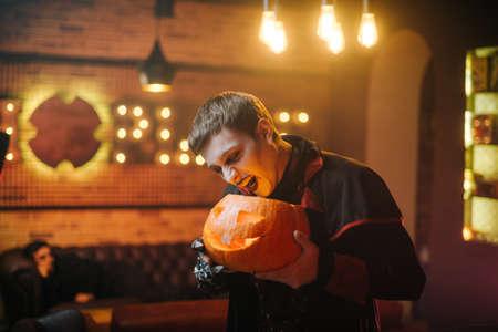 Junger Mann im Halloween-Kostüm des Grafen Dracula hält einen geschnitzten festlichen Kürbis in der Hand und versucht unheilvoll, sie zu beißen.