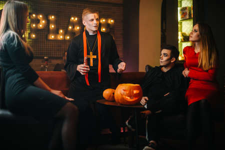 Bunch of three friends having fun celebrating Halloween at cafe. Guy is dressed as terrible priest and monster. Beautiful sexy girl in red dress. Carved pumpkin on table