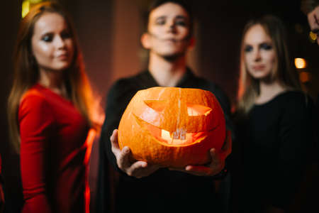 Group of friends celebrating Halloween. Young man wearing zombie costume holds pumpkin on his outstretched arm. Two girls looking at pumpkin. Peoples faces are blurred, camera focuses on pumpkin Imagens