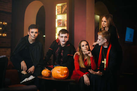 Portrait of friends in Halloween costumes sitting in a cafe and looking at the camera