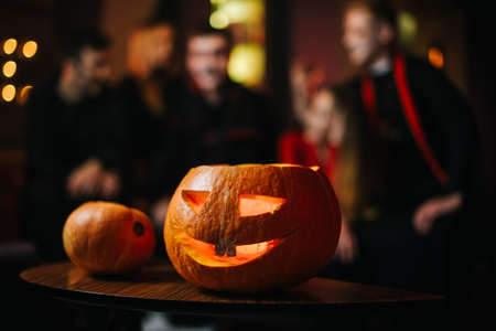 Halloween carved pumpkin on the table at the cafe. Against the background of a group of friends celebrating on the eve of Saints Day. Theres a candle burning inside the pumpkin Imagens