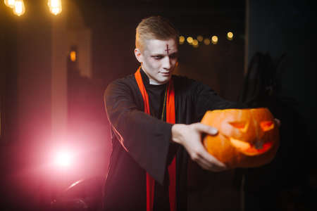 Young man in a Halloween costume holding a carved pumpkin on his outstretched arm. The pumpkin is blurry, the cameras focus is on the guys face.
