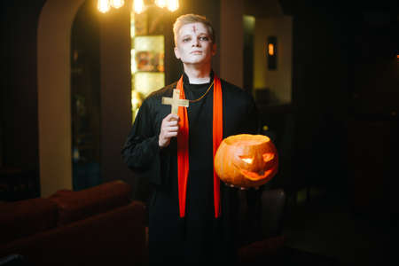 Young man in a Halloween priest costume holds a carved pumpkin and a religious cross. Guy looks into the camera