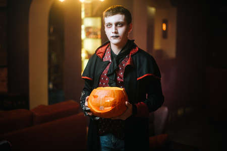 Guy in Count Draculas Halloween costume is holding a carved pumpkin in his hand.