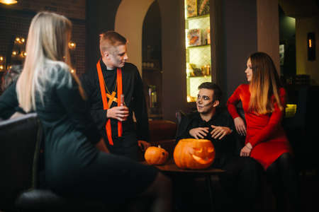 Young people in costumes are celebrating Halloween. Group of young cheerful guys and girls dressed in Halloween clothes are chatting in cafe. Carved pumpkin on the table