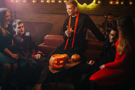 Friends in colorful festive costumes and with makeup on their faces have fun at Halloween party in a cafe. Carved pumpkin on table