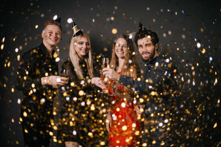 Two attractive guys and two beautiful girls are clinking with champagne glasses and celebrating new year. On friends from above the festive confetti falling. Shooting on isolated black background. Stock Photo