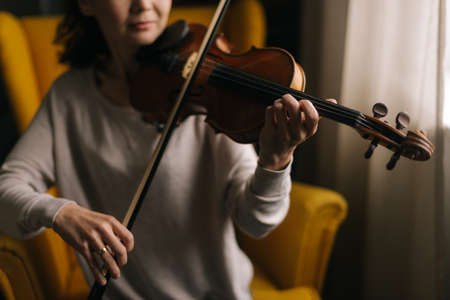 Schöne junge Musikerin, die Geigennahaufnahme spielt und auf einem weichen Stuhl im Zimmer mit modernem Interieur sitzt. Mädchen übt das Spielen von Musikinstrumenten zu Hause. Standard-Bild