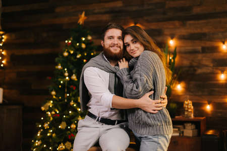 Beautiful couple posing against the background of a Christmas tree. Happy man hugging with girlfriend and look at the camera.