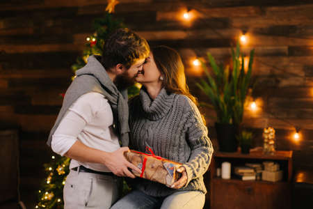 Guy kisses his girlfriend by the Christmas tree. Young man gives New Year present to his girlfriend. Girl with smile accepts gift from her husband. Couple is hugging on New Year Eve.
