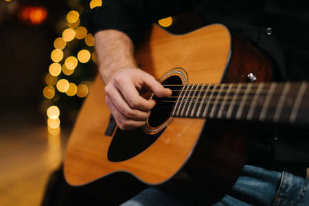 Man plays guitar close-up. Against the background of a decorated Christmas tree with a bokeh effect.