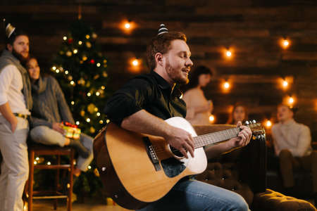 Portrait of young happy man in the festive hat singing with guitar. against the background of talking friends. Christmas tree with garland and wall with festive illumination in background.