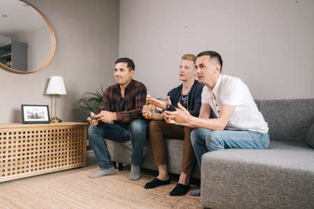 Group of three friends sitting on soft couch in living room and playing video games at home. Young man holds bottle of beer in his hands and comments on game of his comrades.