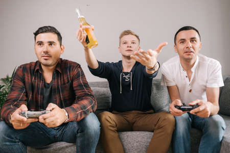 Friends come together and play in the console game. Young man holds bottle of beer in his hands and comments on game of his comrades.