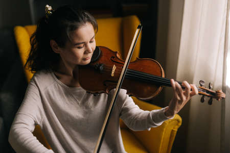 Pretty young woman playing the violin close-up, sitting on soft chair in room with a modern interior. Girl is practicing playing musical instrument at home. Stok Fotoğraf