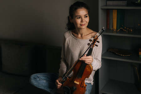 Young woman posing with a violin at home sitting on the couch. Girl is posing with musical instrument.