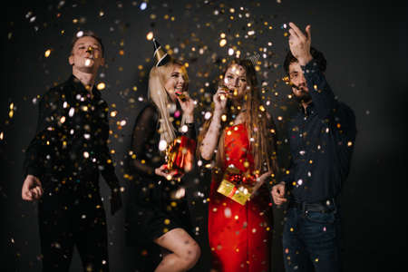 Two cheerful guys blow a festive whistle and throw up a colorful confetti. Two beautiful happy girl are holding bright gift boxes in hands. Shooting in professional studio on isolated black background Foto de archivo - 135414670