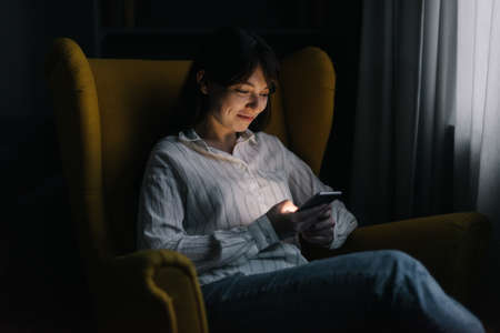 Pretty young woman is using phone in dark room. Attractive girl sits on soft yellow chair. Modern evening pastime.