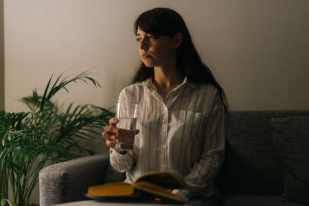 Beautiful young woman keeps a glass of water in a dark room. On the table is a book. Girl looks away.
