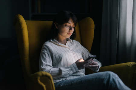 Beautiful young woman is using phone in dark room. Attractive girl sits on soft yellow chair. Modern evening pastime.