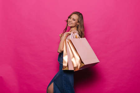 Attractive young woman with colorful paper bag after shopping in mall on isolated pink background. Cheerful girl in denim clothes posing with packages on season sale in professional studio.