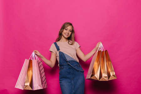 Cheerful young woman in denim clothes posing with colorful shopping bags on isolated pink background in professional studio.