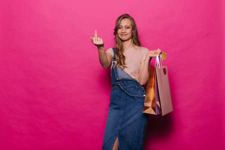 Beautiful young woman is showing middle finger, gesture fuck you Charismatic girl is showing concept of emotions in professional studio on isolated pink background..