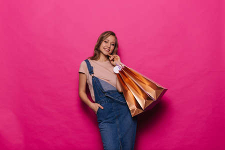 Excited stylish woman holding colorful shopping bags on isolated pink background. Cheerful girl in denim clothes posing with packages on season sale in professional studio.