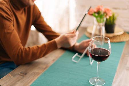 高い赤ワイングラスのクローズアップ。男はバックグラウンドでデジタルタブレットを使用しています。