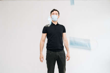 Portrait of young excited man wearing protective mask throwing medical masks as if they were money bills, on isolated white background. Prevention of virus infection. Imagens